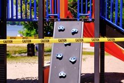 Children playground closed due to coronavirus pandemic lockdown. Yellow caution tape restricting the slide and climbing equipment.