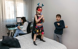 Children playing and dancing on the bed while their mother works in pajamas at home. Conciliation family work concept