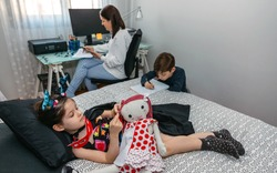 Children playing and doing homework while their mother works at home. Conciliation family work concept