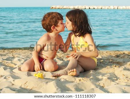 Children playing and kissing on the beach