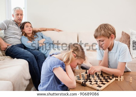Children playing chess in front of their parents in a living room