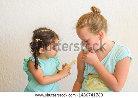 Children playing doctor. Doctor injecting vaccination Flu Shot in arm little child girl, healthy and medical concept.