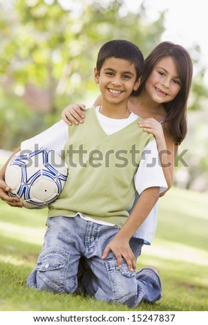 Children playing football in park looking to camera