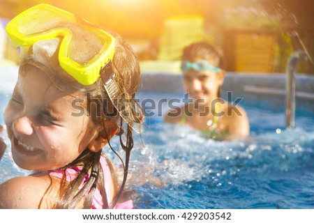 Children playing in pool. Two little girls having fun in the pool. Summer holidays and vacation concept #429203542