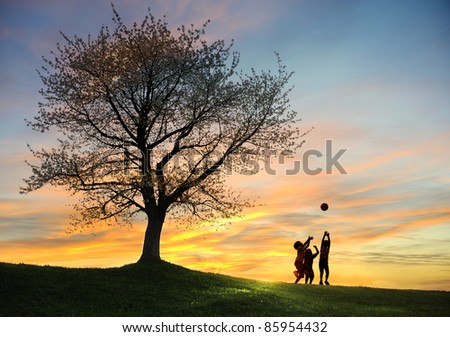 Children playing in sunset with ball, silhouettes, freedom and happiness