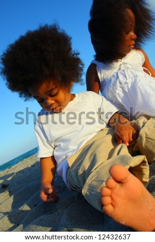 Children playing in the sand with a foot in the foreground