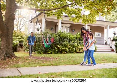 Children Playing On Garden Swing And Scooter Outside House