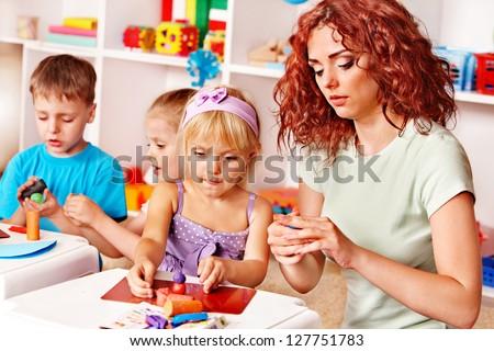 Children playing plasticine in kindergarten.