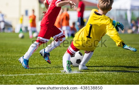 Children Playing Soccer Football Match. Youth Soccer Forward and Goalkeeper Duel. Football soccer game. Players footballers running and playing football match. Forward footballer against goalkeeper.