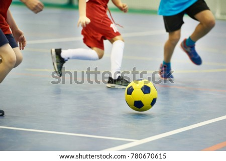 Children playing soccer with yellow football indoors #780670615