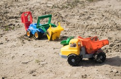 children playing toys on the beach. Plastic colorful dumptruck and bulldozer. Childhood memories. Fun in a sandpit. summer outdoor activity. Toy vehicle in sand.