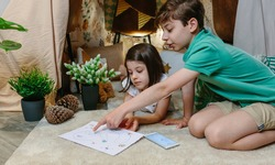 Children playing treasure hunting game in a diy tent at home. Home vacation concept