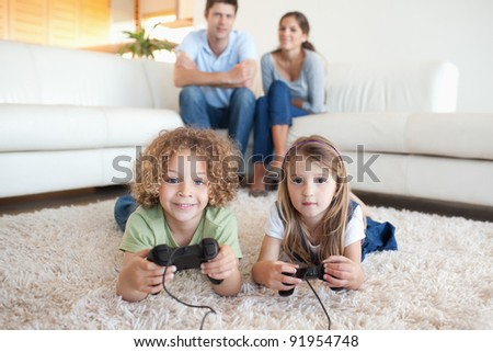 Children playing video games while their parents are watching in their living room