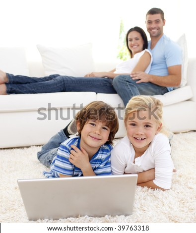Children playing with a laptop on floor and parents lying on sofa