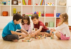 Children playing with blocks on the floor - focus on the boy's face
