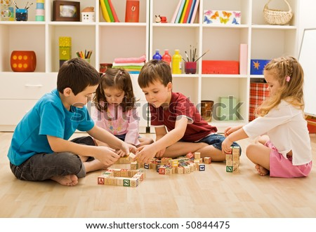 Children playing with blocks on the floor - focus on the boy\'s face