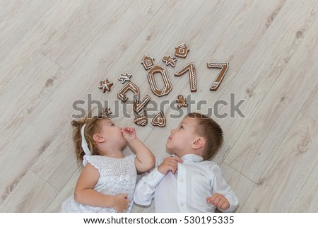 Children playing with gingerbread New Year\'s Eve.