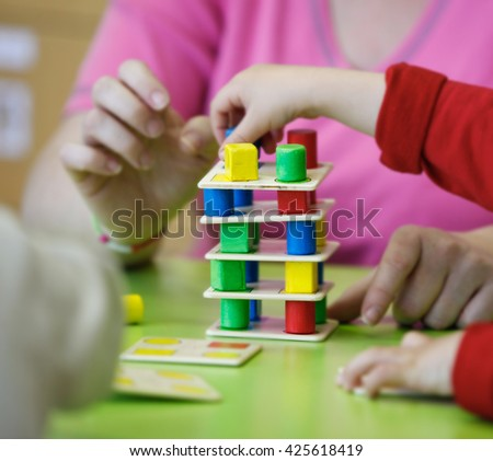 Children playing with homemade, do-it-yourself educational toys, stacking and arranging colorful pieces. Learning through experience concept, gross and fine motor skills, back to school concept.