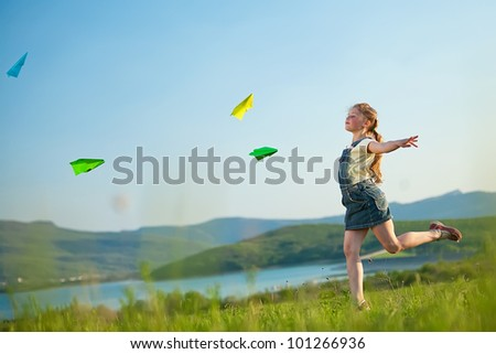 Children playing with paper airplane in the open air
