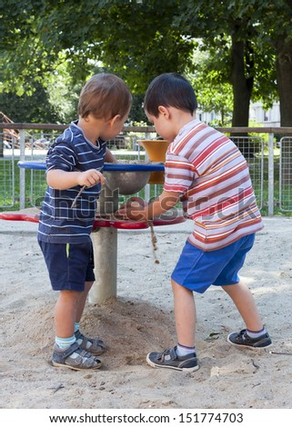 Children playing with sand at playground on a play table equipment.