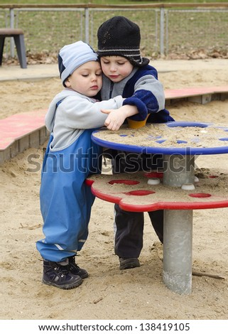Children playing with sand in a playground on a cold day.