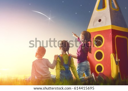 Children playing with toy rocket and dreaming of becoming a spacemen. Portrait of funny kids looking at the sky. Family friends games outdoors. Boy and girls make a wish by seeing a shooting star.