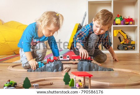 Children playing with wooden train. Boy and toddler girl play with railroad and cars. Educational toys for preschool and kindergarten child. Cute kids at home or daycare interior #790586176