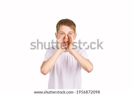 Children portrait in white t-shirt. Studio isolated concept. Shout rumor. Secret gossip. Modern communication. Boy hold hand near head Foto stock ©