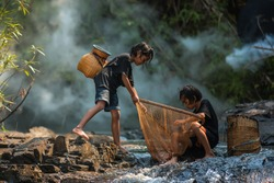 Children poverty living in countryside Vietnam are fishing at the river.