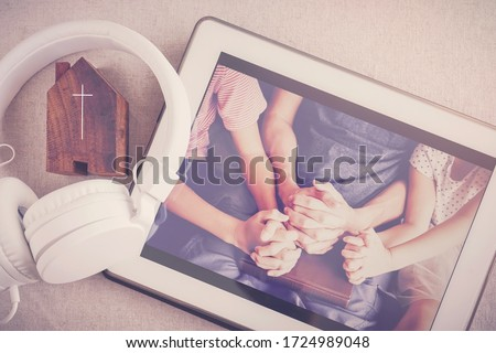 Children praying with father parent with  digital tablet, family and kids worship online together at home, streaming online church service, social distancing, new normal concept