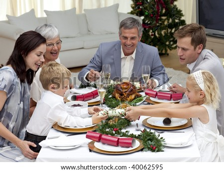 Children pulling a Christmas cracker at home in a family dinner