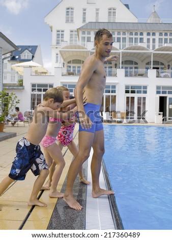Children pushing man in pool