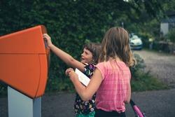 Children putting a postcard in the mailbox