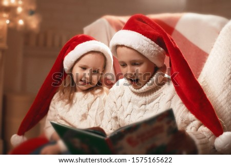 children read bedtime stories on their own.Merry Christmas and happy holidays! Cheerful cute little baby boy and his sister girl with book. kid reads a fairy tale near the Christmas tree in the room.
