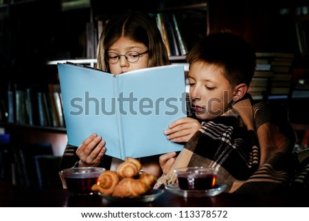 Children reading book at night