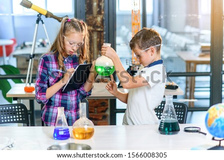 Children record results of the experiments in notebook. Two young clever caucasian pupils in protective glasses doing experiment with green liquid in beaker and dry ice.