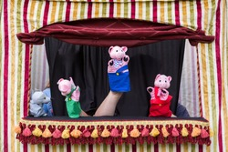 Children reenacting the story of the three little pigs and the big bad wolf with hand puppets in small puppet theater