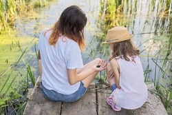 Children resting near the water on sunny summer day, two girls looking at lake sitting on bridge, relaxing, playing with water snails, back view