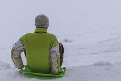 Children ride a slide in winter