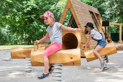 Children riders on wooden swing with spring on the playground in the park. Two girls ride on the playground in summer