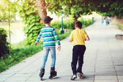 Children riding on scooter and roller skate at street. Back view of friends spending time together outside. Active outdoor sport for kids. Friendship, leisure and lifestyle concept.