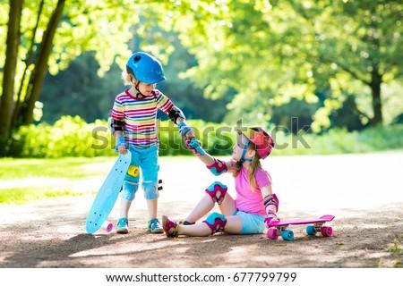 children riding skateboard in...