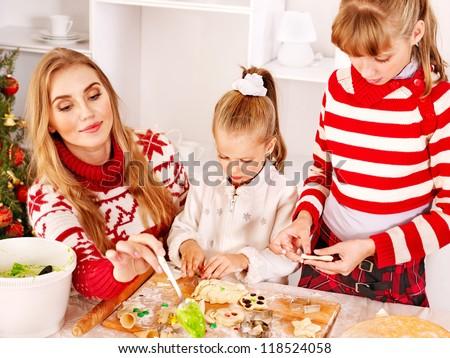 Children rolling dough in Xmas kitchen.