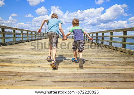 Children run on a wooden pier. Boys hold hands and run on the bridge. Back view