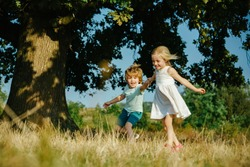 Children run on field. Happy children girl and boy running on meadow in summer in nature. Happy little farmers having fun on field. Cute toddler girl and boy working on farm outdoors