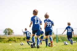Children Running After Balls on Soccer Training Camp. Kids Practicing Football on Grass Field. School Boys Kicking Soccer Balls
