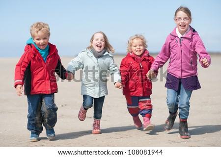 Children running at the beach - stock photo