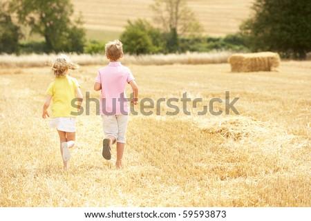 Children Running Through Summer Harvested Field