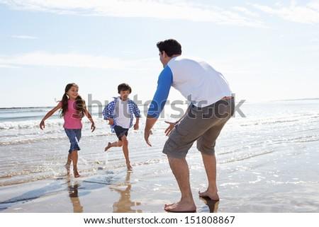 Children Running Towards Father On Beach