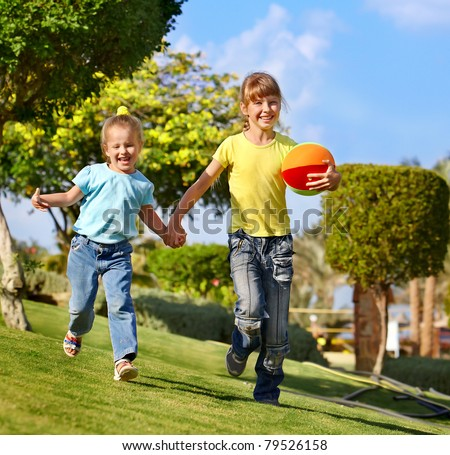 Children running with ball in park. Outdoor.